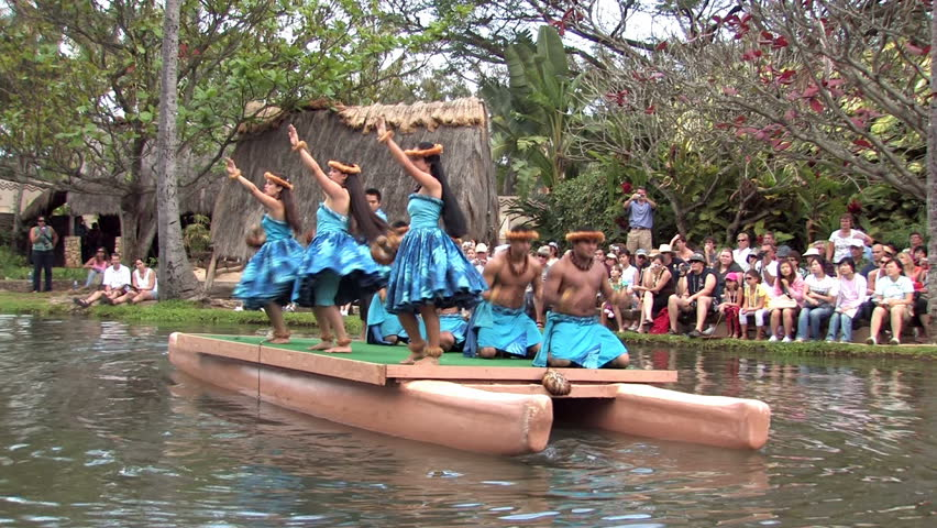Polynesian Cultural Center in Laie Oahu Hawaii. Canoe show with dancers from Hawaii. Tourists on the main lagoon. Blue skirts on beautiful dancers. Water, lagoon and palm trees. - HD stock video clip