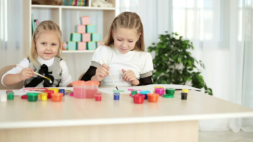 Sister whispers in your ear. They are painting at the table  - HD stock footage clip