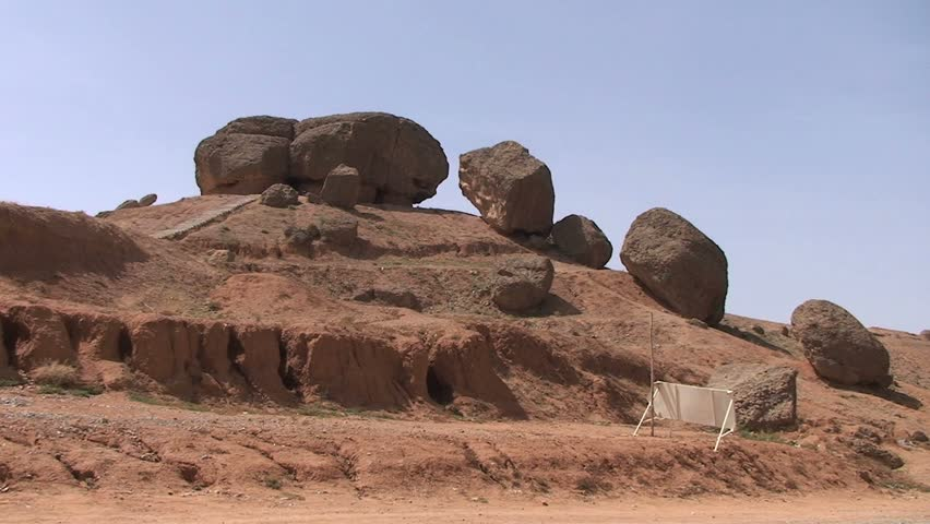 Kid with backpack walks past boulders on hilltop - HD stock video clip