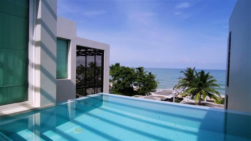 Swimming pool of a luxury villa. Tracking shot.