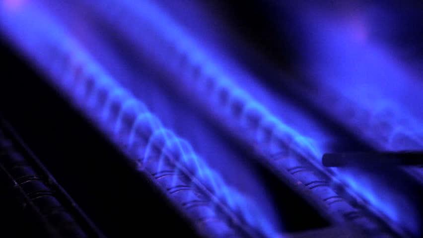 Blue flames of a gas burner inside of a boiler