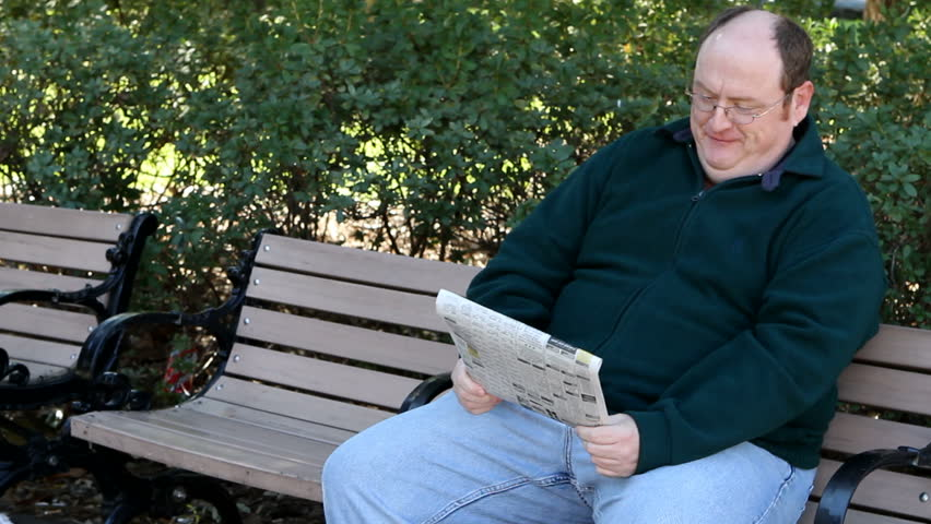 Overweight man sits on a park bench reading the newspaper. - HD stock footage clip