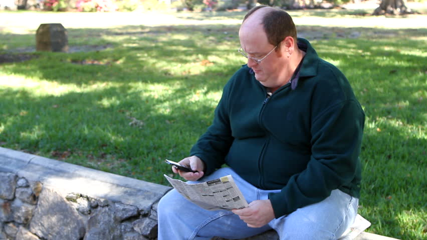 Unemployed obese man uses a cell phone to call about a job in the want ads section of the newspaper while in the park. - HD stock footage clip
