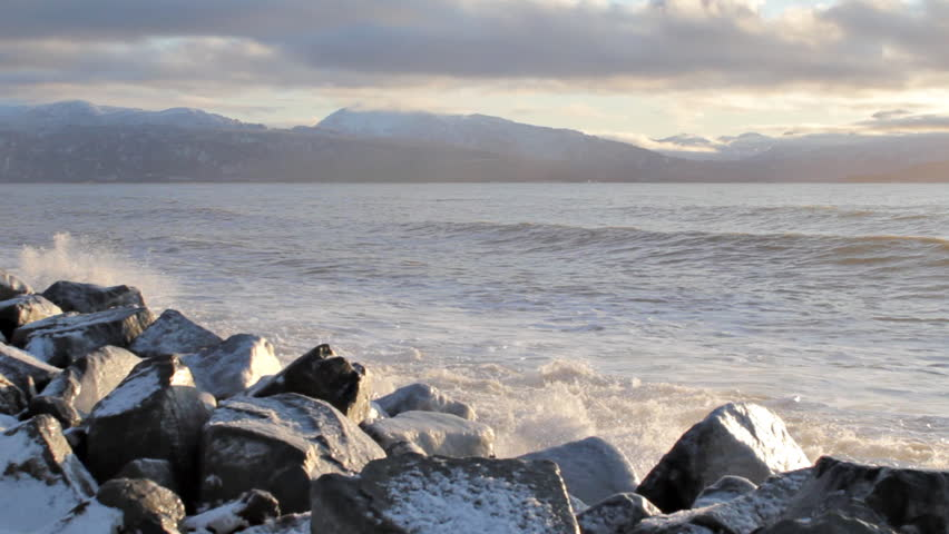 Large waves crashing on icy rocks on the Homer Spit in Alaska. - HD stock video clip