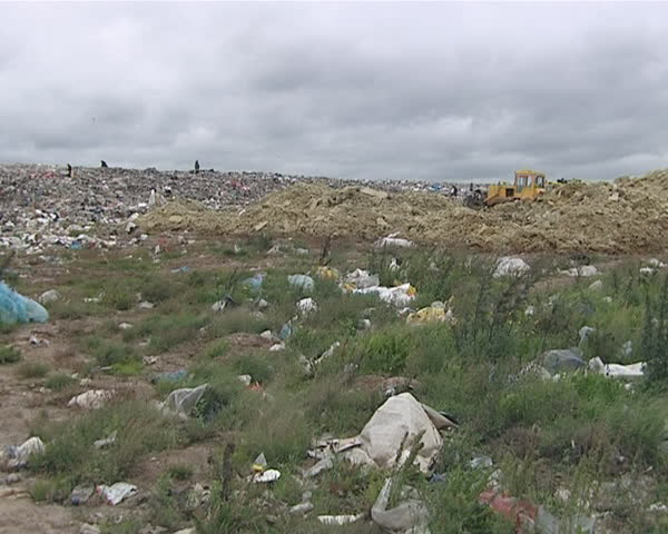 Garbage handling equipment and homeless people looking for food and survival items in dump. Environmental pollution. Poverty.  - SD stock footage clip