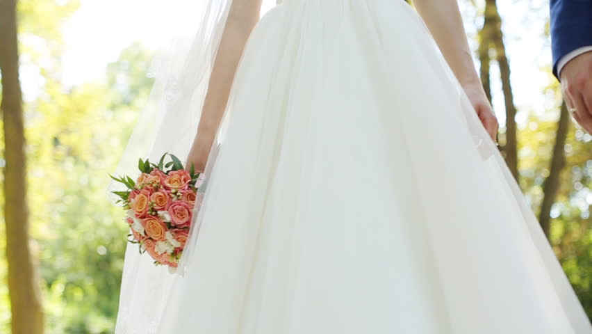 Wedding couple tenderly holding each other hands, bride holding bouquet of roses close up   Shutterstock HD Video #18713402