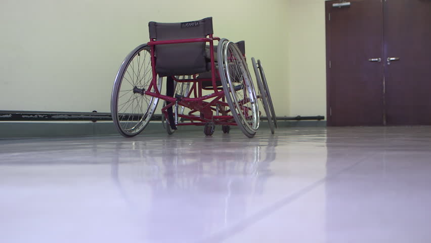 Wheelchairs. MCU view of manual wheelchairs in a long empty corridor. The wheelchairs are reflected in the shiny floor. (Abu Dhabi - UAE-2013) | Shutterstock HD Video #18738737
