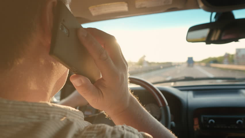 Over the shoulder shot of a man answering the phone and talking while driving on a busy road in the sun. | Shutterstock HD Video #18746027