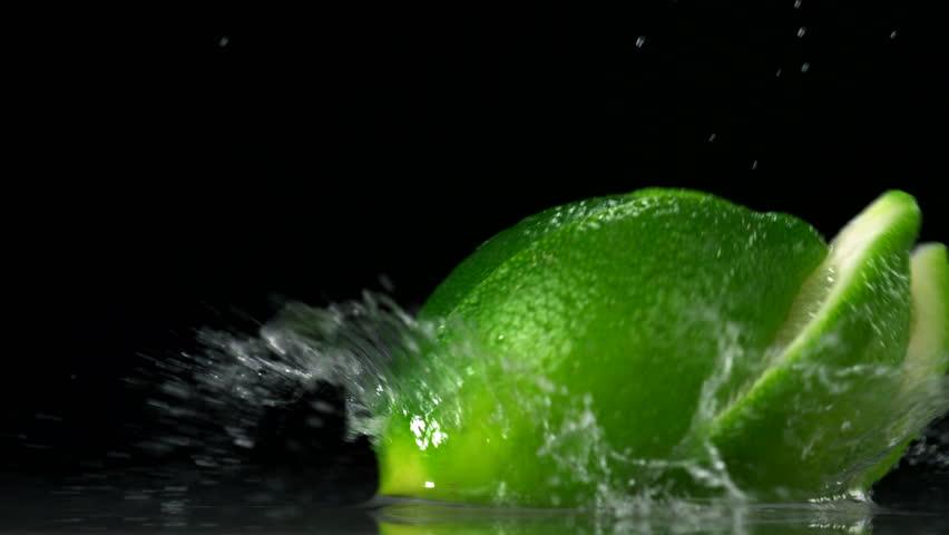 Slo-motion lime wedges falling against black drop