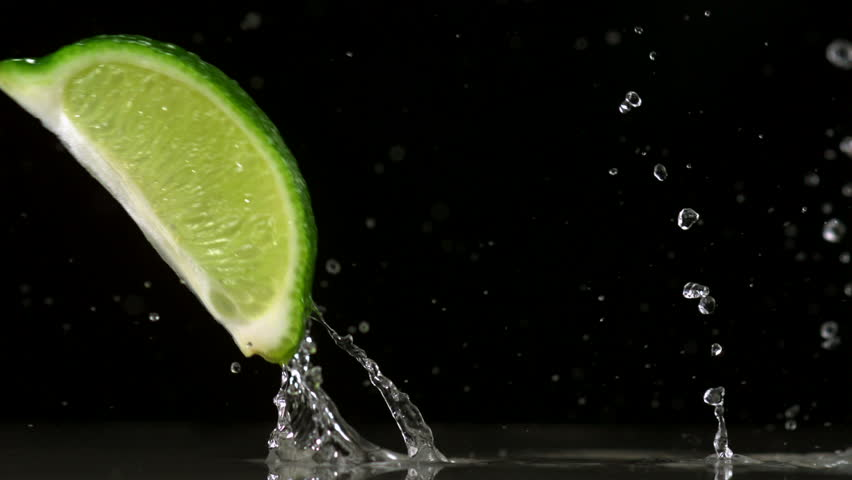 Slow-motion lime wedges falling against black drop