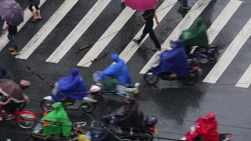 July.17,2015-Hangzhou,China: people wearing colorful rain coat, riding bikes on zebra crossing in raining day | Shutterstock HD Video #18843668