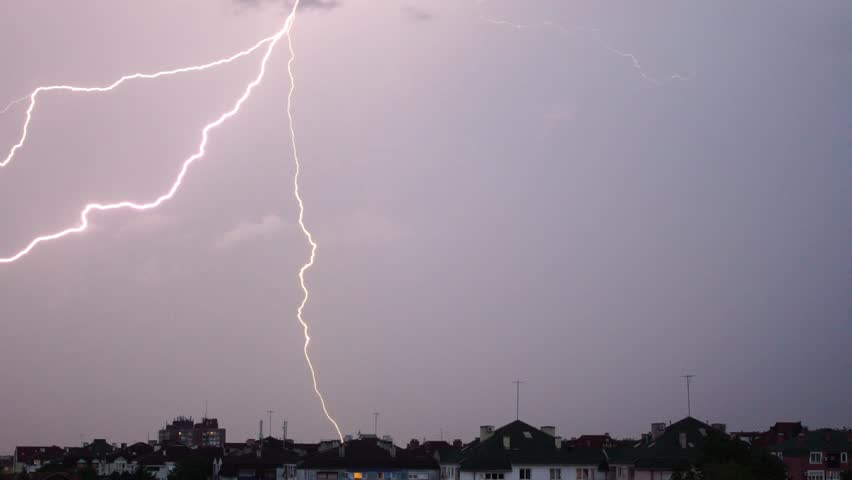 SLOW MOTION: Night sky above the city skyline during a thunderstorm, with the whole sky being lit by a lightning and branching lightning bolt. Sequence of multiple clips.