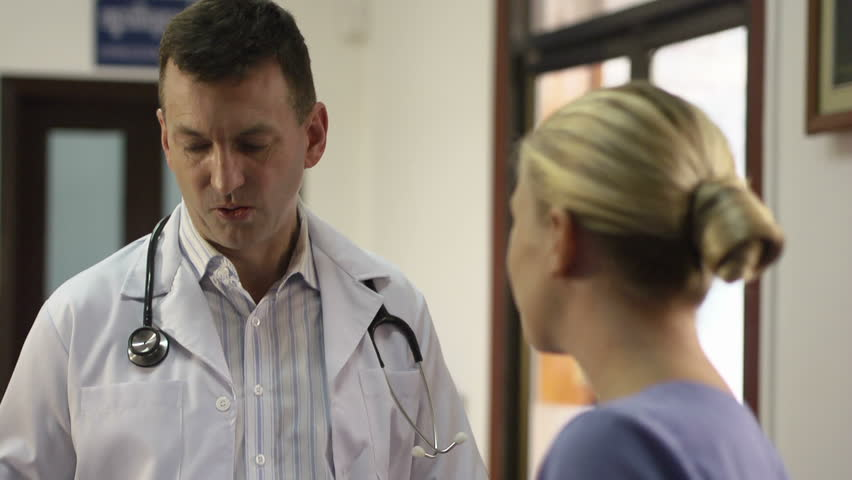 Doctor talking to young woman at work as nurse in medical clinic and taking medical file. Rack focus - HD stock video clip