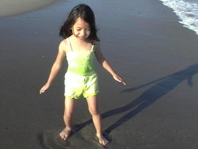 little asian girl chasing waves