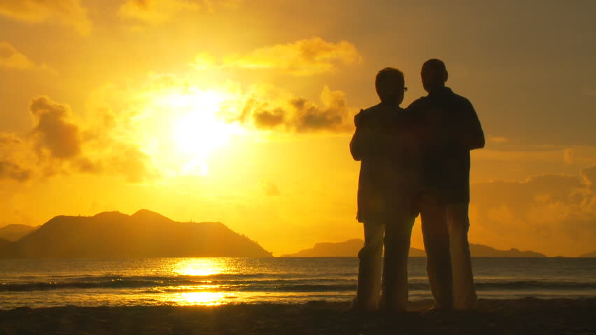 elderly couple cheering on beach at sunset