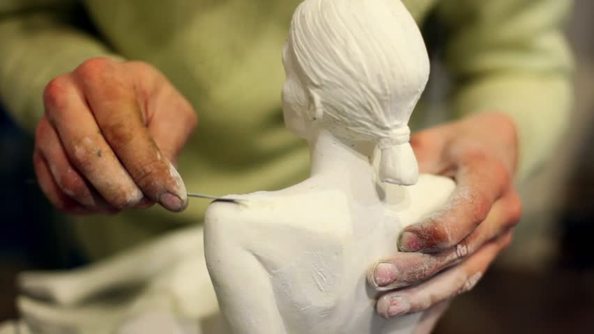 Sculptor corrects arm of female figurine by special tool - HD stock video clip