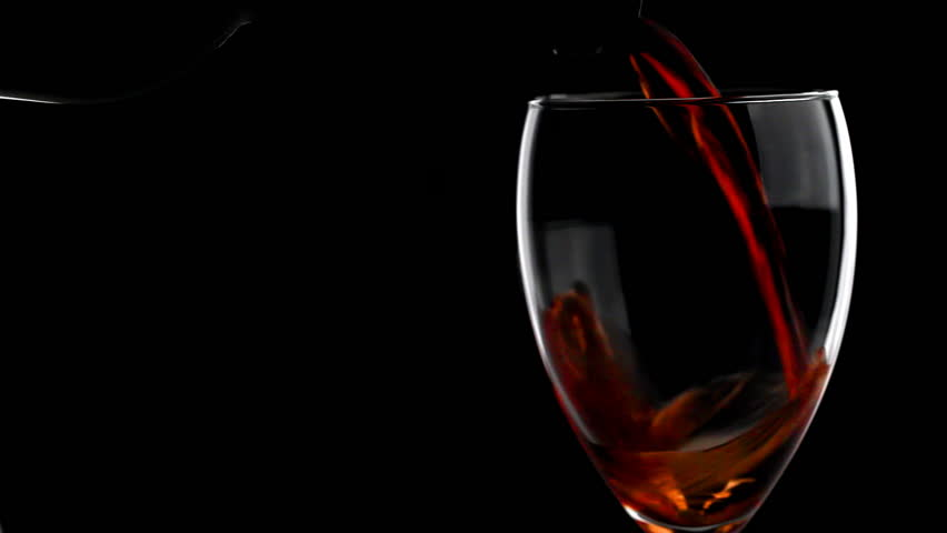 Red Wine Poured Into Glass Isolated On Black Background