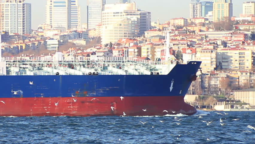 Oil tanker sails in front of the city. Bow of the large ship