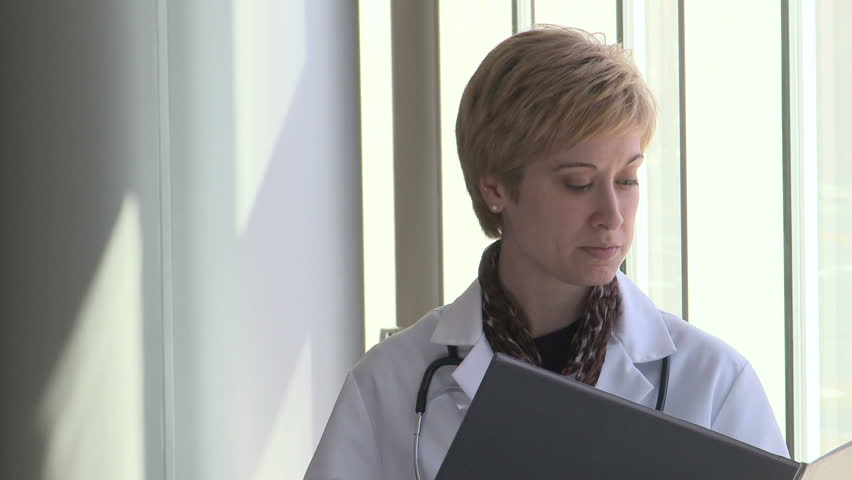Woman doctor looks at patients chart then looks a the camera with a worried look - HD stock video clip