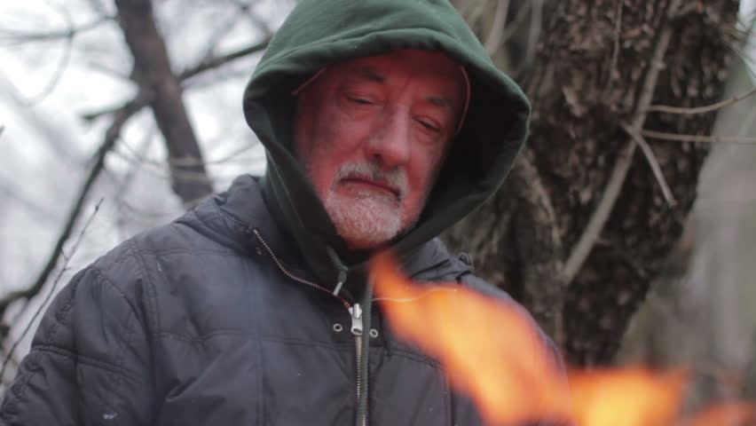 Homeless man in front of a fire, close up - HD stock footage clip