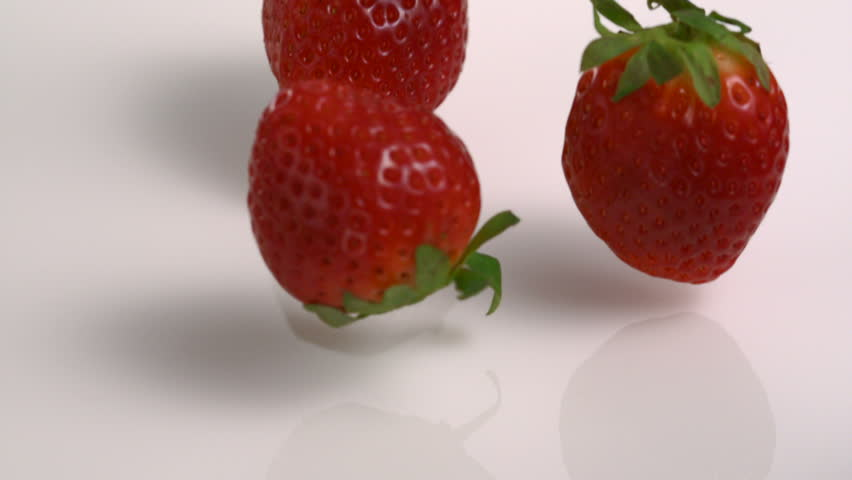 Slow-motion strawberry into milk - HD stock footage clip