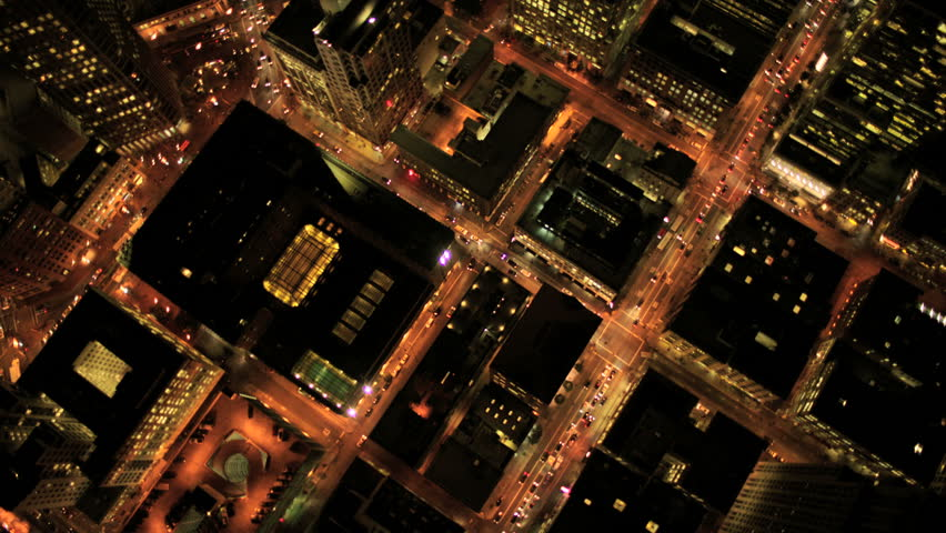 Aerial night vertical view of skyscraper rooftops and illuminated streets in a modern city - HD stock footage clip