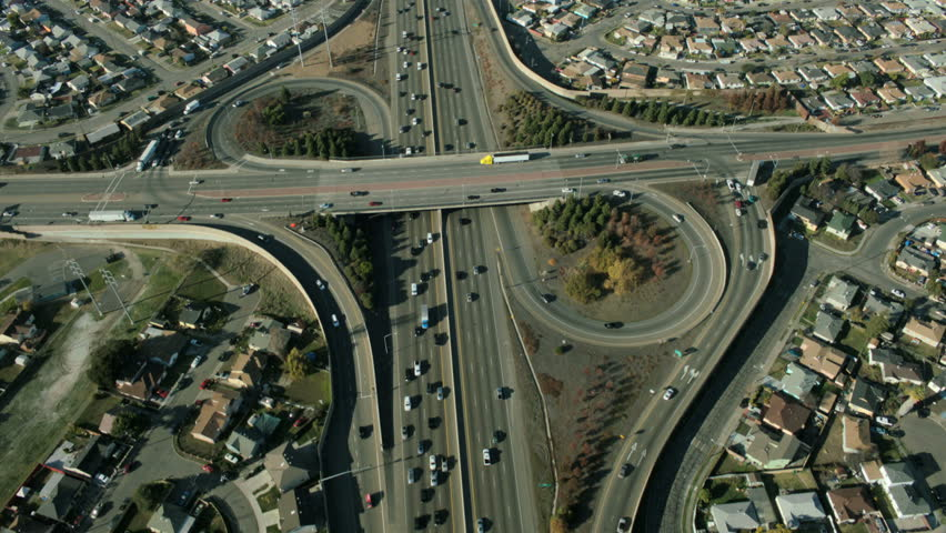 Aerial view of busy city traffic at an intersection on a major freeway in the suburbs of the city