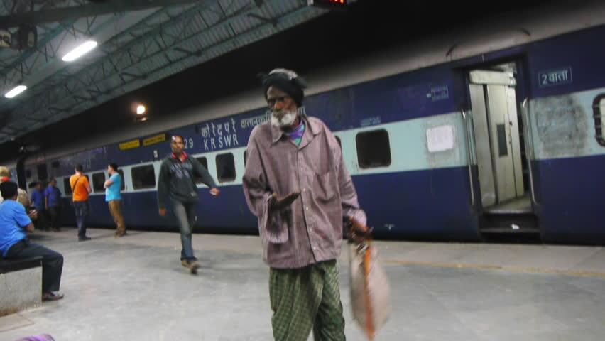 MUMBAI, INDIA - FEB 1: Old man begs and men move baskets at a railway station February 1, 2012 on Chhatrapati Shivaji Terminus (formerly Victoria Terminus) Mumbai, India. - HD stock video clip
