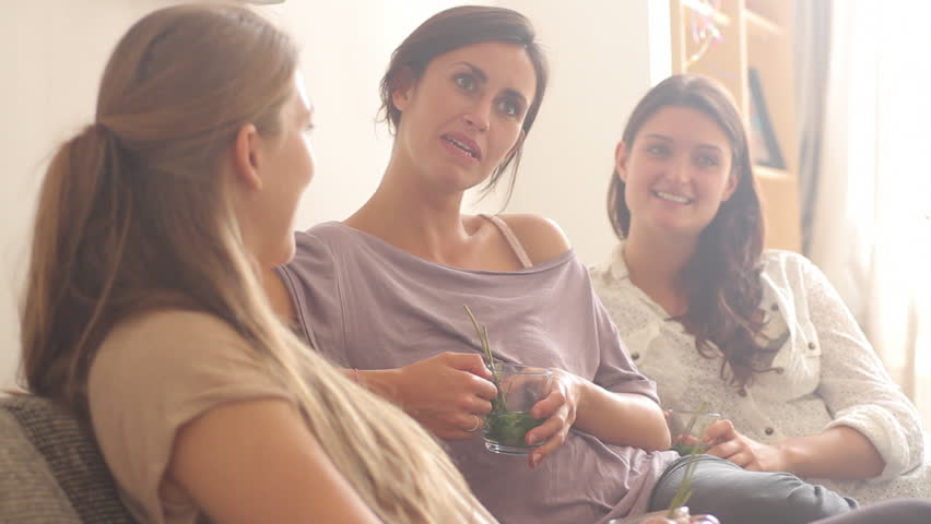 Female friends sitting on sofa drinking tea and chatting - HD stock footage clip