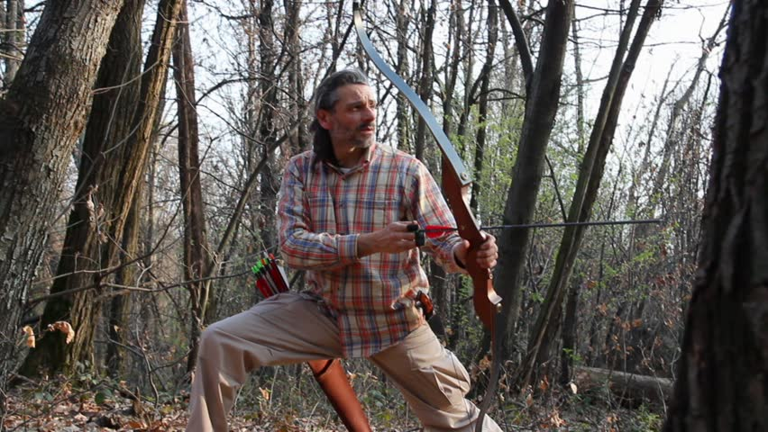 man shooting with traditional bow in the forest - HD stock footage clip