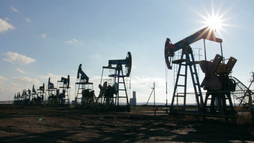 working oil pumps silhouette against sun  - HD stock video clip