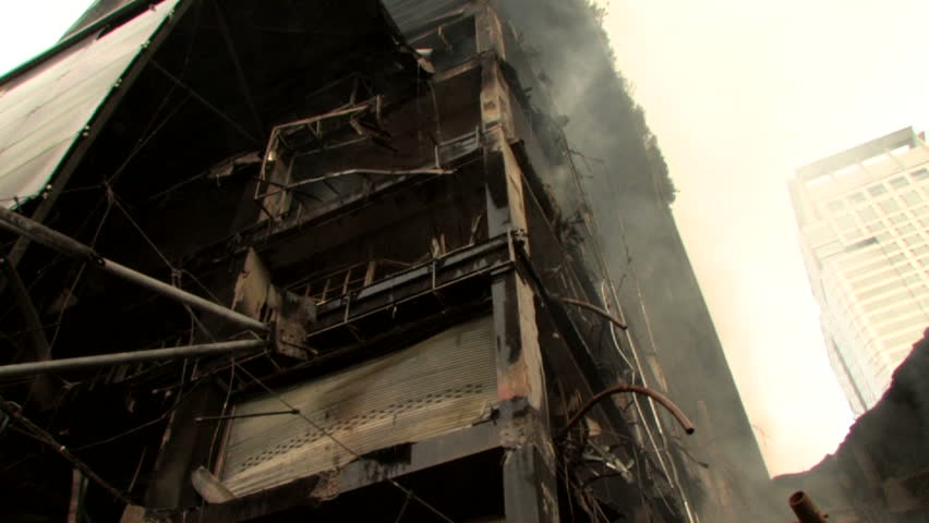 Building devastated by bomb attack fire arson smoking ruins  - HD stock video clip