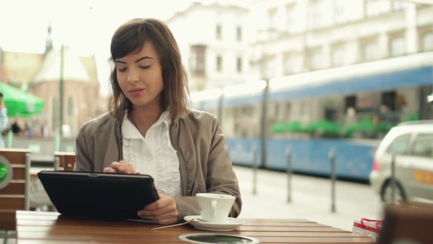 Woman with tablet computer drinking coffee in city
