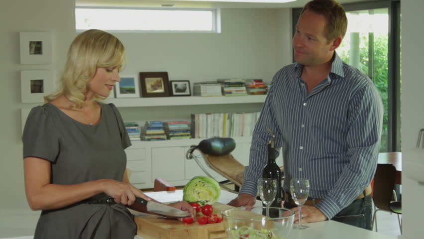Wide shot off couple in kitchen preparing a healthy salad and opening a bottle of wine to celebrate - HD stock video clip