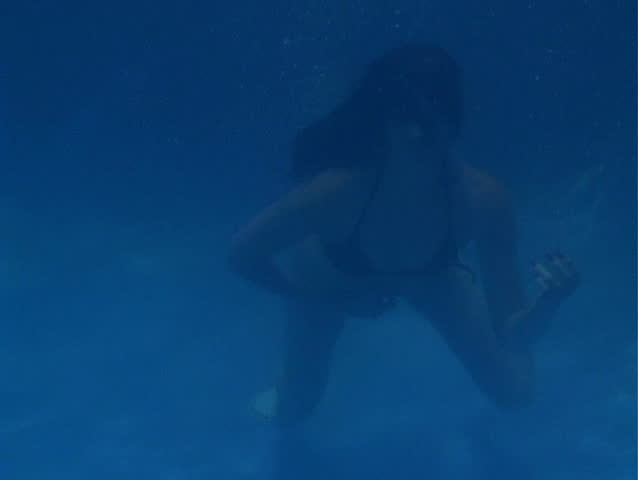 A beautiful brunette in a bikini plays an air guitar underwater.  Add your own guitar track for an exciting and attention-getting clip! - SD stock footage clip
