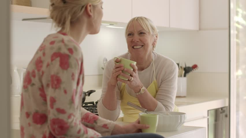 Happy women in home kitchen, mom and daughter talking and drinking a cup of tea