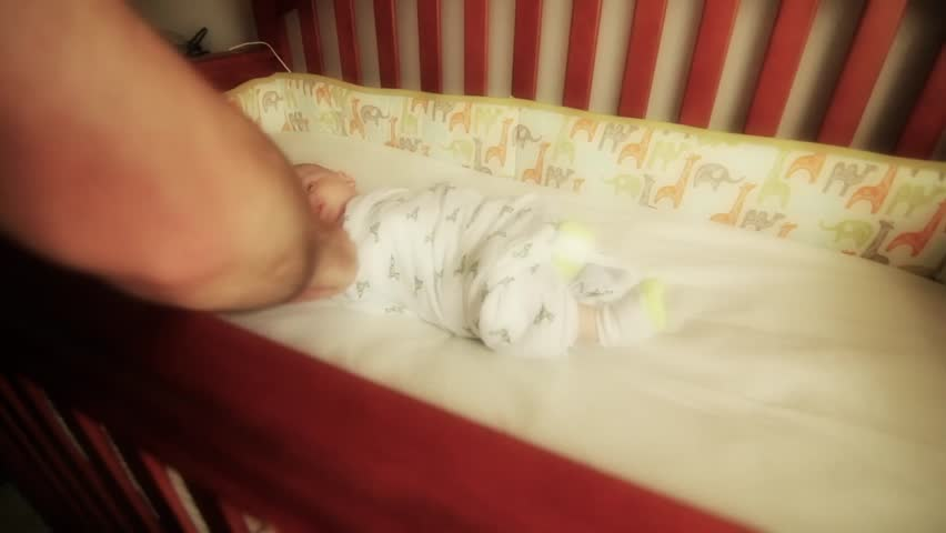 A father un-swaddles his baby boy in his crib - HD stock video clip