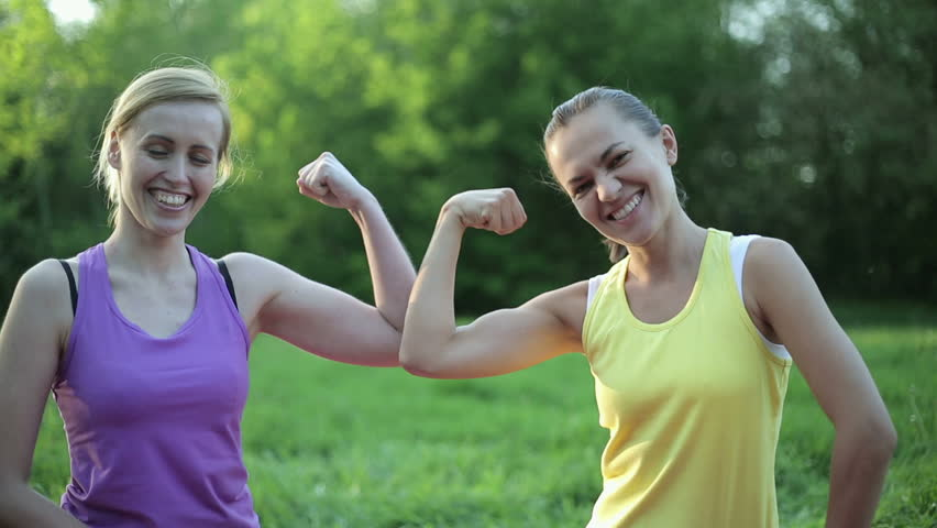 Portrait of two fit young women flexing her biceps, tracking shot
