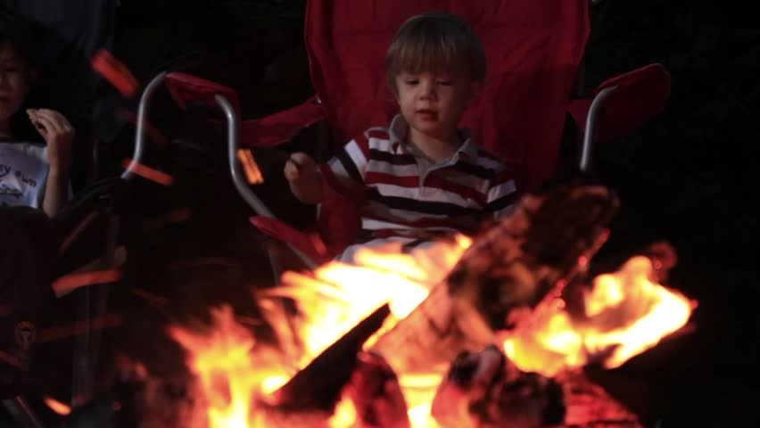 Two kids boys sitting roasting marshmallows at campfire - HD stock footage clip