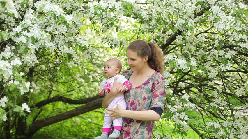 Mother and baby in blossoming apple orchard - HD stock video clip