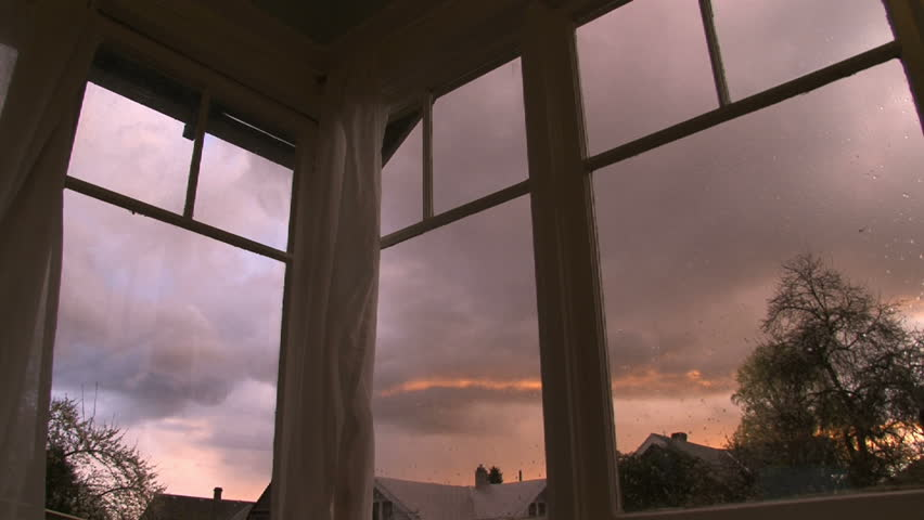 Full sunset time lapse through old windows in house. Rain clouds develop and