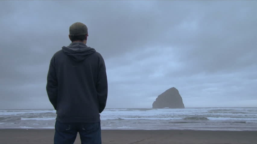 Time lapse of night clouds and man standing, watching Pacific Ocean.