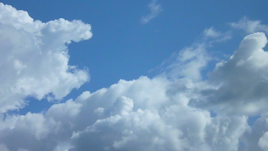 Large clouds slowly move together on blue sky day time lapse.