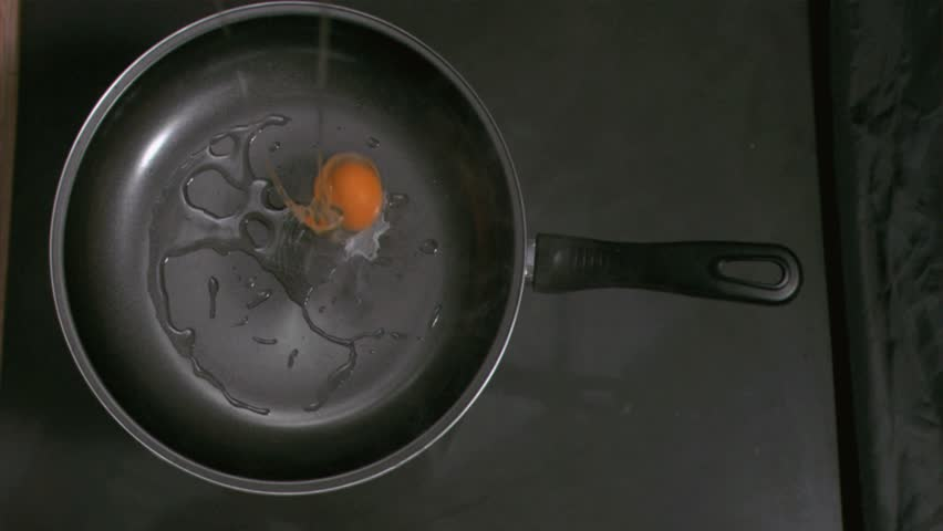 Egg in super slow motion falling in a pan in the kitchen