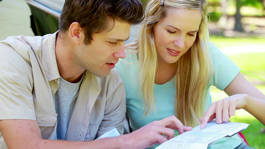 Couple looking a map while camping in a park - HD stock video clip