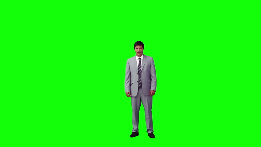 A happy man in a suit is jumping against a green background - HD stock video clip