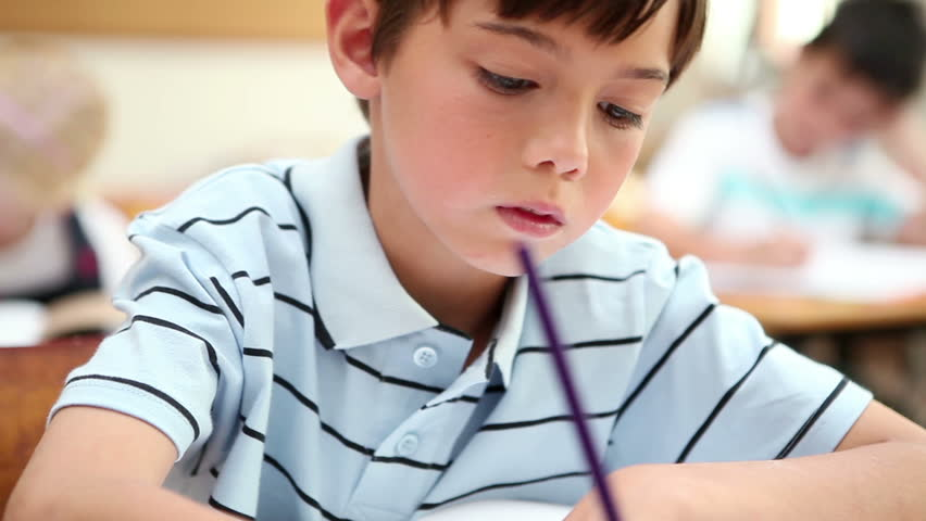 Pupil writing on his notebook in the classroom - HD stock video clip