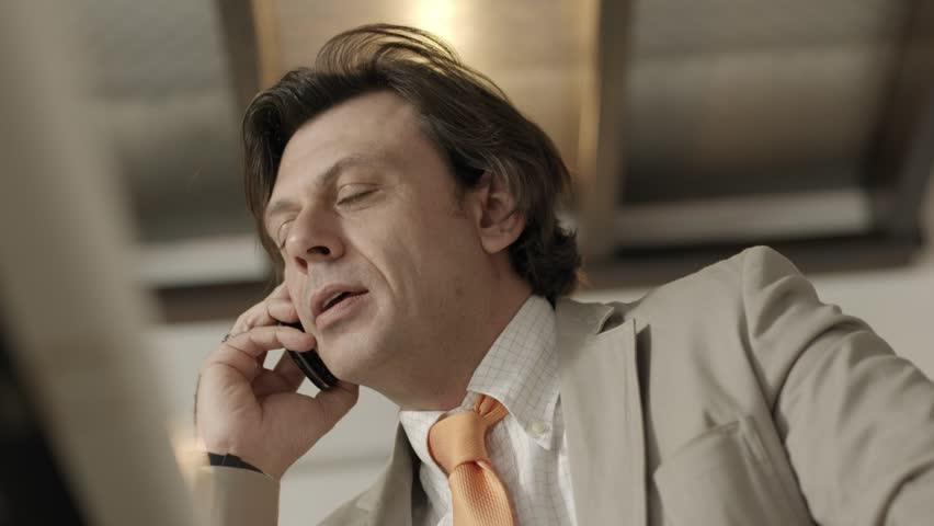 Adult businessman at work in office and talking on mobile phone. Low angle view - HD stock footage clip
