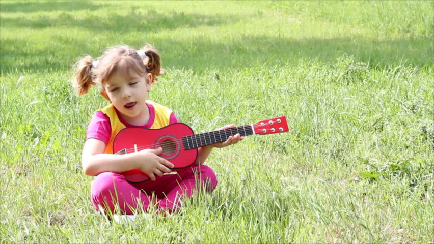 little girl sitting on grass and playing guitar - HD stock video clip