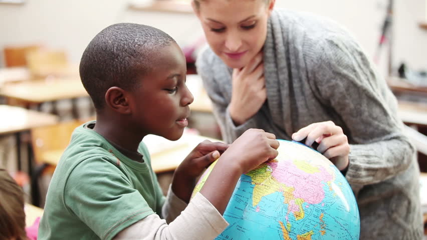 Pupil and teacher looking at a globe in the classroom - HD stock footage clip